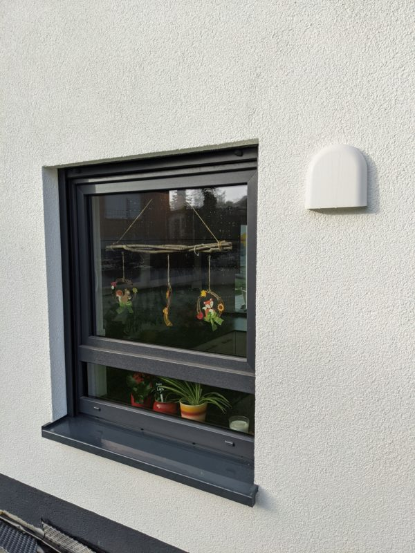 Weiße Außenblende Lüftungsgerät neben Anhtrazit Fenster